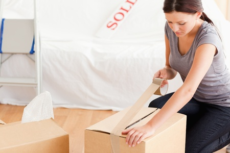 removals: A woman closing a cardboard with tape