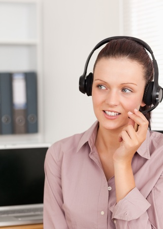 Smiling Young woman with headphones in an office photo