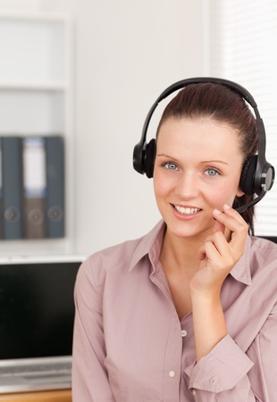 Red-haired woman with headset in an office photo