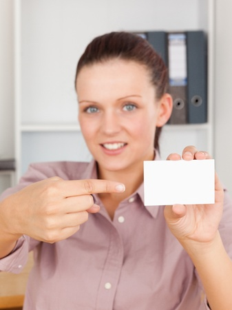 Red-haired business woman pointing at a card in an office photo