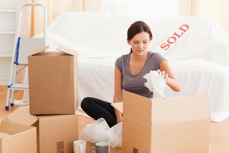 Gorgeous woman packing her property in her old house photo
