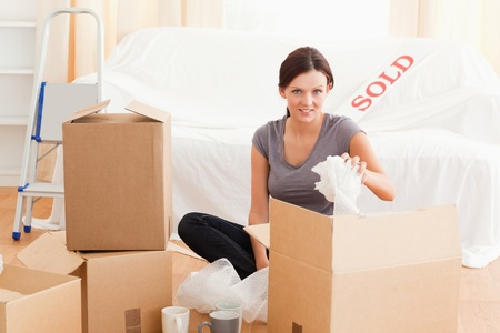 Charming woman packing her property in her former house photo