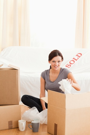 Charming redheaded woman packing her property in her former house photo