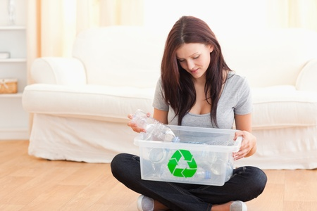 Cute woman putting bottles in a recycling box in her home photo