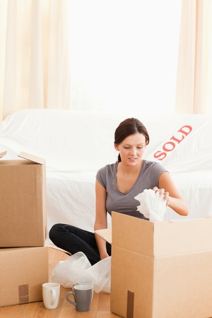 Cute woman packing her things in her former home photo
