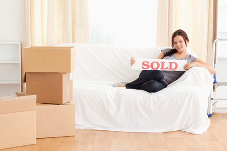 Cute woman holding a sold-sign in a living room photo