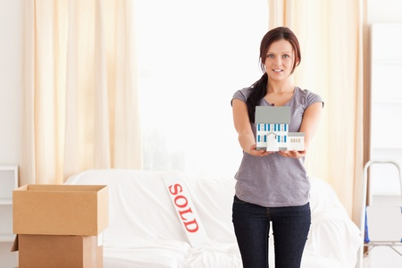Young woman holding a model house in a living room photo