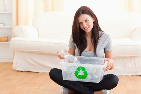 reusing: Cute woman with a recycling box in a living room