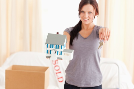 Beautiful woman holding model house and keys in a living room photo