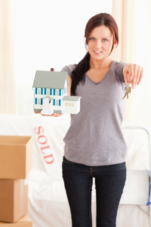 Portrait of a woman holding model house and keys in a living room photo