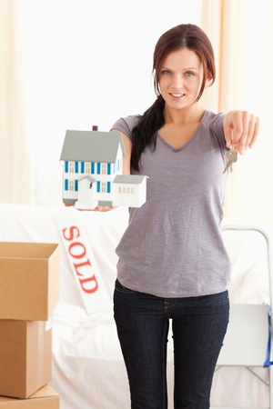 Portrait of a woman with model house and keys in a living room photo