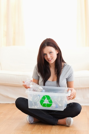 reusing: Gorgeous woman with a recycling box in a living room Stock Photo