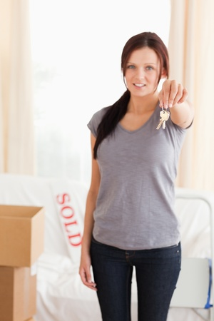 Portrait of a Cute woman holding keys in a living room photo