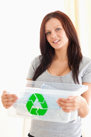 Gorgeous woman holding a recycling box in a living room photo
