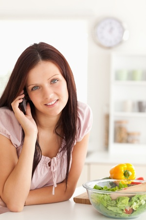 Cute woman using a cellphone in a kitchen photo