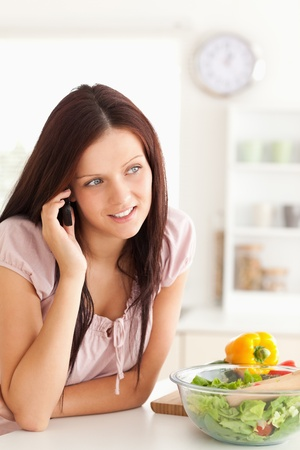 Charming woman using a cellphone in a kitchen photo