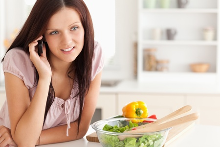 Smiling woman using a cellphone in a kitchen photo