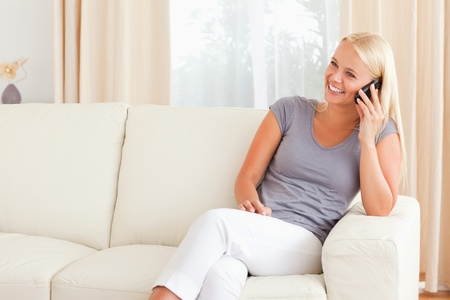 Laughing woman on the phone in her living room photo