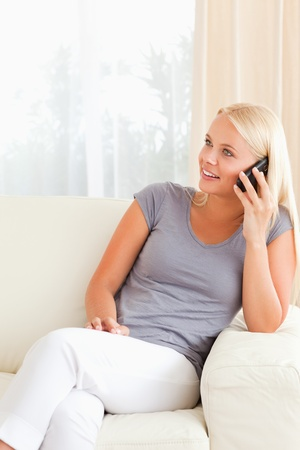 Portrait of a blonde woman on the phone in her living room photo