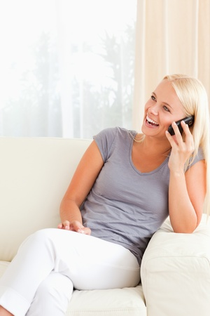 Portrait of a laughing woman on the phone in her living room photo