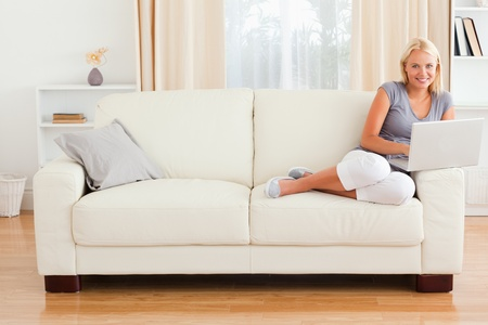 Blonde woman with a notebook in her living room photo