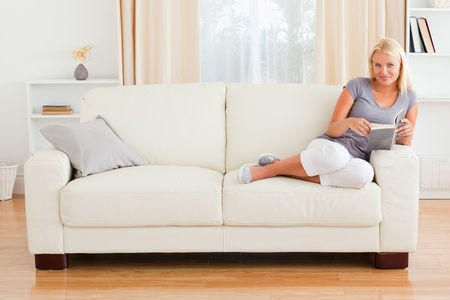 page down: Woman holding a book in her living room Stock Photo