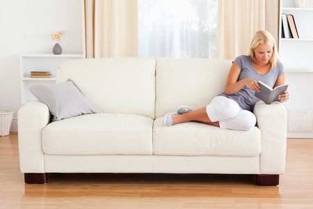 couch: Woman reading a book in her living room