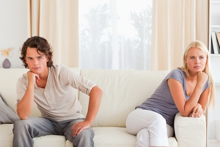 Upset couple sitting on a sofa with their hand on their chin photo
