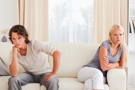 contented: Sorrowful couple sitting on a sofa not looking at each other
