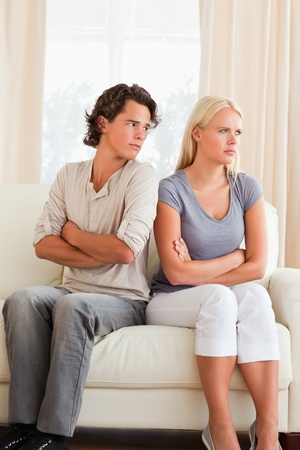 Portrait of a young couple after an argument with the arms crossed photo