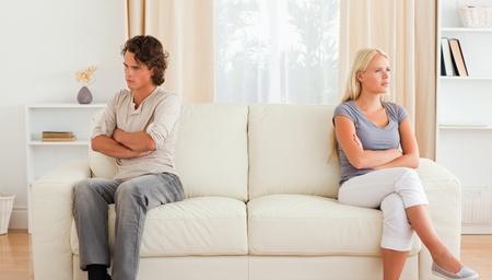 couple fach�: Couple en col�re contre l'autre assis sur un canap� Banque d'images