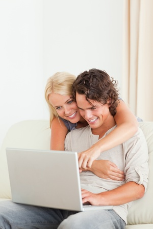 Portrait of a happy couple using a laptop in their living room photo