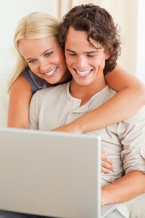 Portrait of a happy couple using a notebook in their living room photo