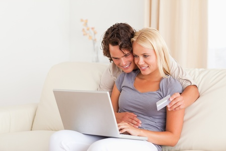 Lovely couple shopping online in their living room photo