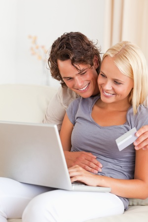 Portrait of a lovely couple shopping online in their living room photo