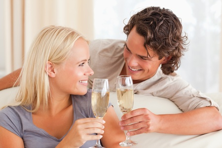 internet love: Couple making a toast in their living room Stock Photo