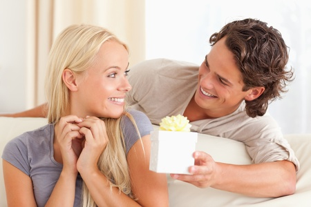 internet love: Man offering a present to his wife in their living room