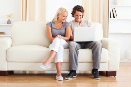couch: In love young couple using a laptop while sitting on a sofa Stock Photo