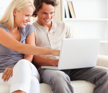 Close up of a couple using a laptop in their living room photo