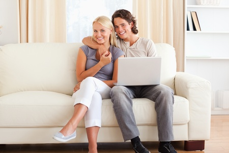Friendly couple with a laptop in their living room photo