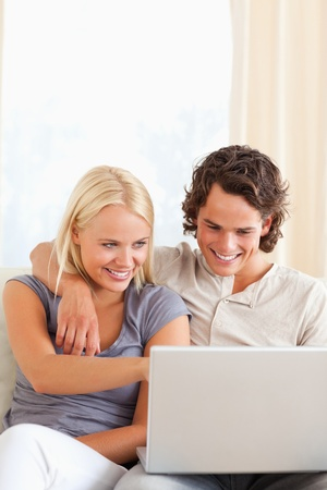 Portrait of a smiling young couple using a laptop in their living room photo