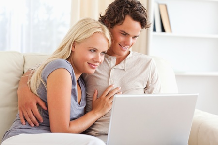 Lovely young couple using a notebook in their living room photo