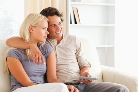 Cute couple watching TV in their living room photo