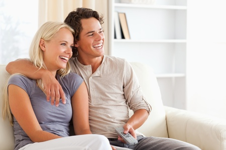 Laughing couple watching TV in their living room photo