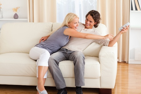 Smiling couple fighting for the remote in their living room photo