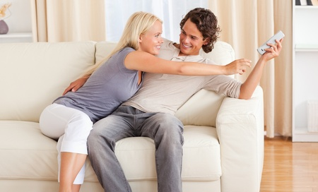 Happy couple fighting for the remote in their living room photo