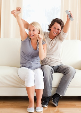 Portrait of a couple cheering up while watching TV photo