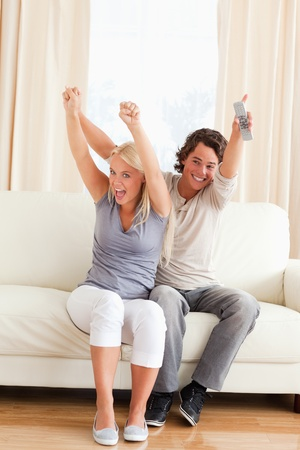 Portrait of a young couple cheering up while watching TV photo