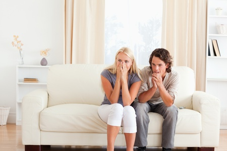 Couple watching a movie on TV in their living room photo