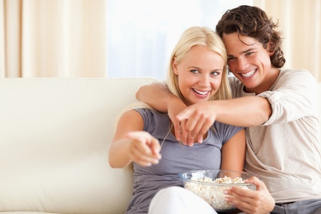 Cute couple watching TV while eating popcorn in their living room photo